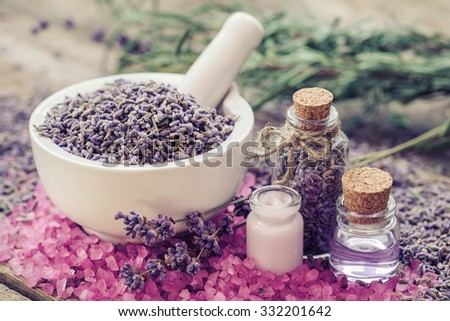 Dry lavender in mortar, aromatic pink sea salt, cream, bottles of essential oil and lavender flowers. Selective focus.  - stock photo