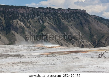 Dry mineral flats with an area of hot steam and water that drops off a ledge with distant mountains in Yellowstone National Park. - stock photo