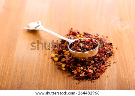 Dry mix of red herbal and fruit tea over wooden surface - stock photo