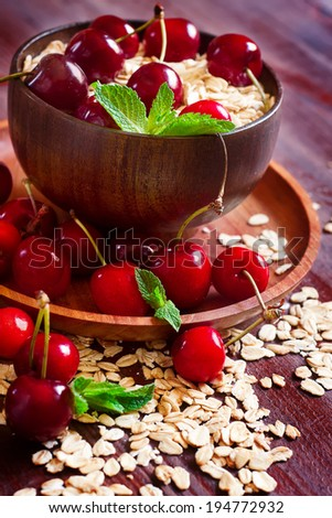 Dry oat flakes with ripe red cherry. Selective focus. - stock photo