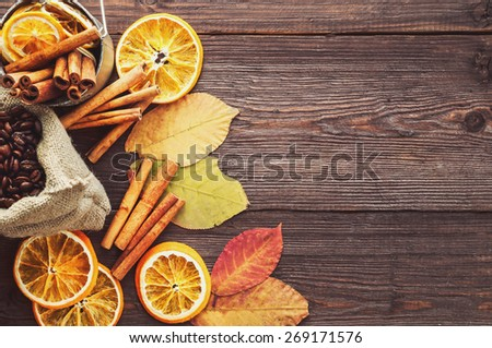 Dry orange and lemon, coffee beans in the bag, cinnamon and fallen autumn leaves on wooden brown background. - stock photo