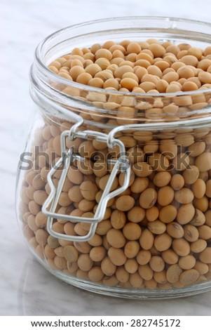 dry organic soybeans, on carrara marble countertop. - stock photo