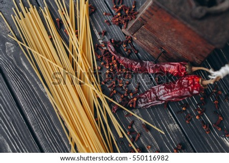 dry paprika, carnation, spaghetti  on a wooden background