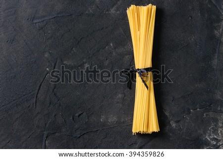Dry pasta spaghetti with black ribbon over black textured background - stock photo