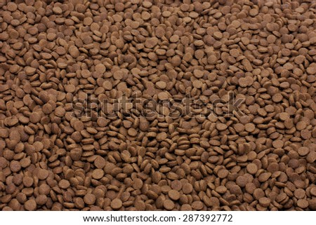 Dry pet food (dog or cat) brown background - stock photo