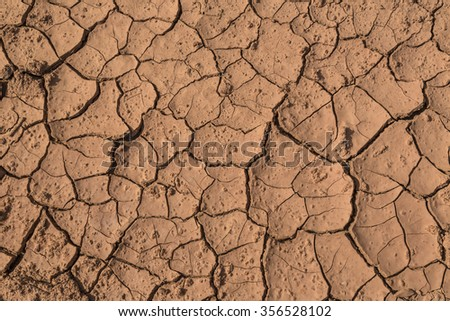 Dry red cracked mud useful as a background or texture. - stock photo