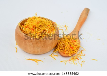 Dry Saffron - Crocus Sativus Tridaceae, in small wooden bowl with teaspoon over white background - stock photo