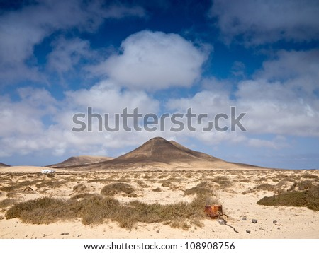 Dry sandy dunes and lonely mountain under cloudy sky - stock photo