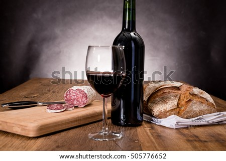 dry sausage delicatessen sliced meat with wine and traditional bread on wooden board