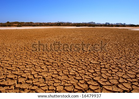 Dry soil detail whit city in the background - stock photo