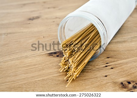 Dry spaghetti in a glass on a rustic wooden background