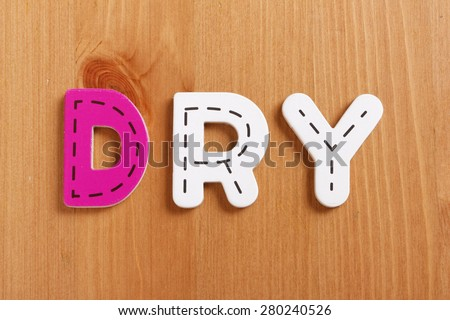 DRY, spell by woody puzzle letters with woody background - stock photo