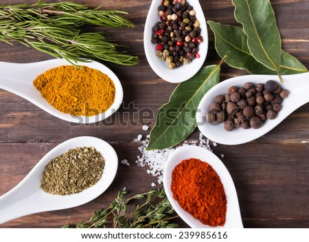 Dry spices and fresh herbs on the wooden table top view