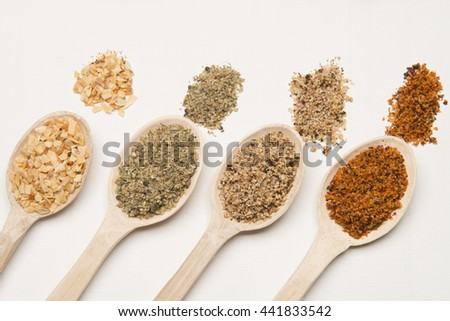 Dry spices on a wood spoons against white background