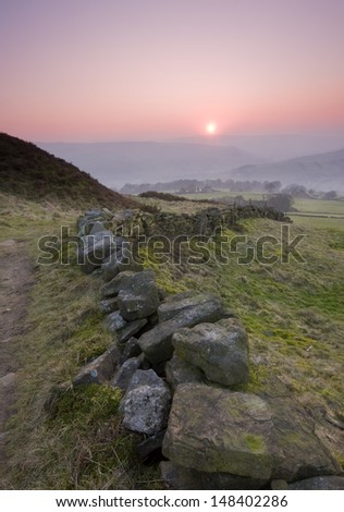 Dry stone wall leading towards a yorkshire misty valley at sunset - stock photo