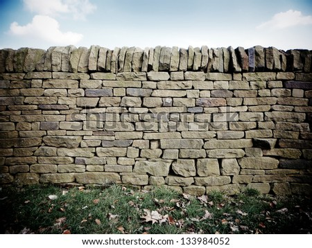 Dry stone wall with fallen leaves - stock photo