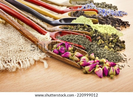 dry tea in scoops on wooden table background - stock photo