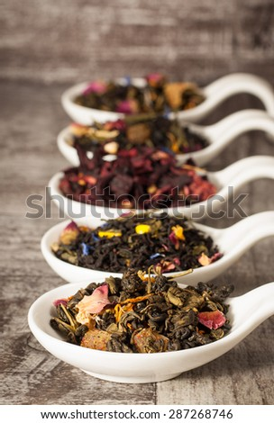 Dry tea in white bowls on wooden rustic background. Leaves of red, green and black tea. Macro photo. - stock photo