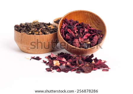 Dry tea in wooden plates, on white background. Leaves of red, green and black tea. Macro photo.