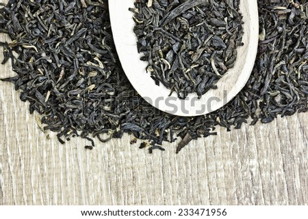 Dry tea leafs texture on wooden table with spoon. - stock photo