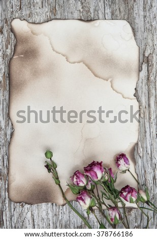 Dry tea roses on the old paper and wooden background