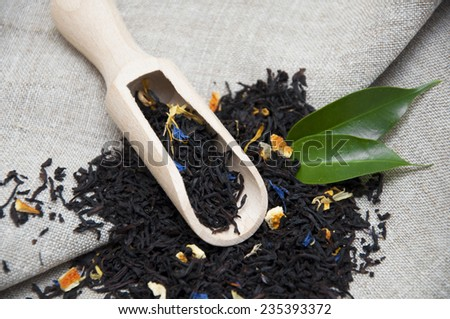 Dry tea with green leaves in wooden spoons