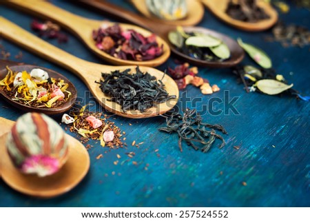 Dry tea with in wooden spoons - stock photo