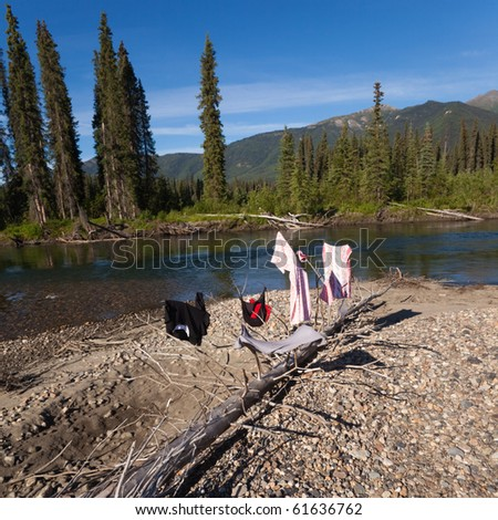 Drying clothes on river bank in pristine wilderness landscape, Big Salmon River, Yukon Territory, Canada - stock photo
