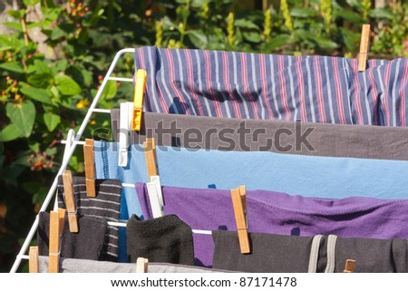 Drying frame with clothes in the garden - stock photo