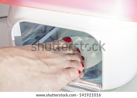 Drying in foot nail enamel drying device, Drying of enamel, series of STEP BY STEP nail varnishing process, HIGH RESOLUTION photos, Closeup, selective focus on nails