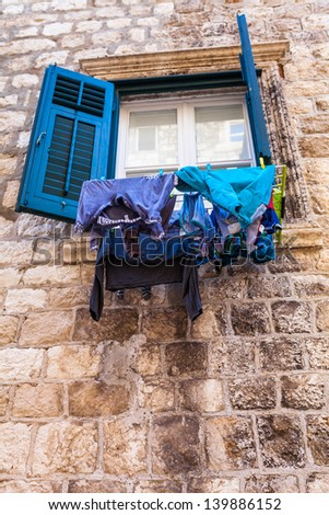 Drying laundry by hanging it on the rope from the window on the narrow street in Dubrovnik, Croatia - stock photo