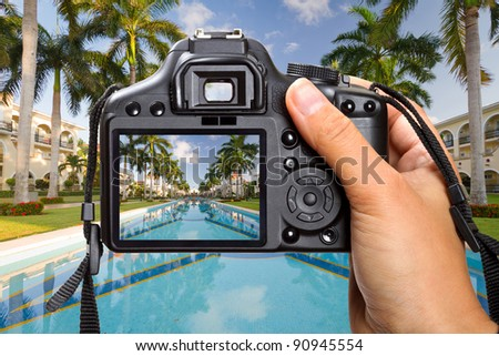 DSLR  camera in hand shooting tropical resort scenery (my photo) - stock photo