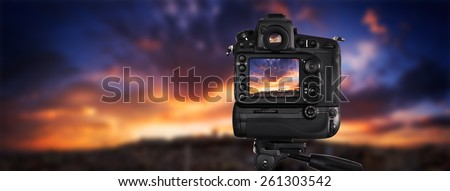 Dslr camera shooting on a cityscape sunset - stock photo