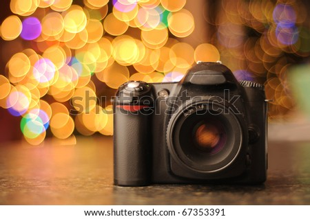 DSLR camera sitting on a black counter top with defocused bokeh background. Copyspace with room for your text. - stock photo