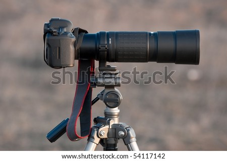 DSLR camera with telephoto lens on a tripod - stock photo