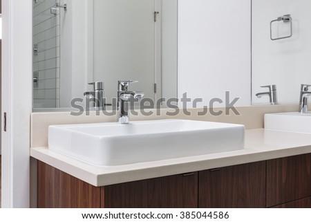Dual modern white sinks with chrome fixtures - stock photo