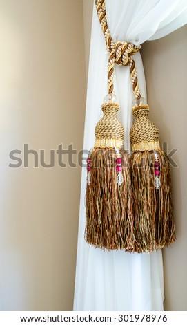 Dual tassels on curtain at main window - stock photo