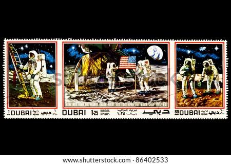 DUBAI - CIRCA 1970's : A stamp printed in DUBAI shows the First men landing on the moon, circa 1970's - stock photo