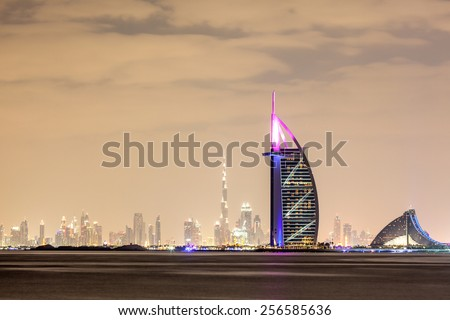 DUBAI - DEC 18: Skyline of Dubai at night with Burj al Arab in foreground. December 18, 2014 in Dubai, United Arab Emirates - stock photo