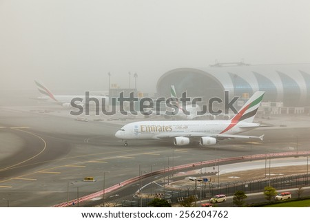 DUBAI - FEBRUARY 21: Emirates A380 is taxiing for take off in a sand storm not in a foggy day as seen on February 21, 2015. - stock photo