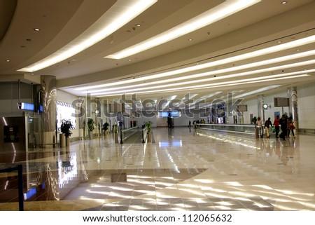 DUBAI INTERNATIONAL AIRPORT, DUBAI-JULY 24: Horizontal escalator well lit Dubai International Airport on July 24, 2012. Dubai International is one of the fastest growing major hubs - stock photo