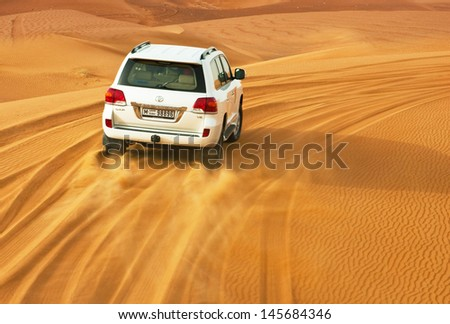 DUBAI - JUNE 2: Driving on jeeps on the desert, traditional entertainment for tourists on June 2, 2013 in Dubai - stock photo