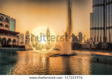Dubai lagoon with fountain against sunset in United Arab Emirates