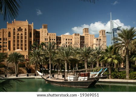 Dubai, Madinat Jumeirah park with the artificial lake and the boat - stock photo