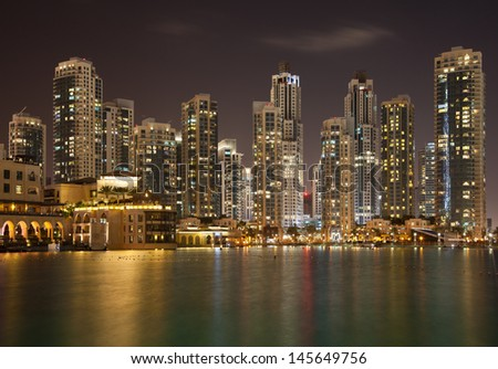 Dubai Skyline and reflection of illuminated skyscrapers on the water.