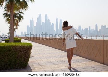 Dubai travel tourist woman on vacation in the Palm Jumeirah walking on embankment. Lady in sexy white dress visiting the famous place. UAE summer destination.