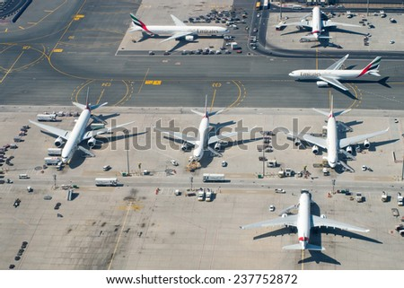 DUBAI, UAE - APR 7:  Planes at Dubai Airport on Apr 7, 2014 in Dubai, UAE. Dubai International Airport is the largest airport in United Arab Emirates - stock photo