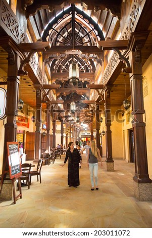 DUBAI, UAE - 1 APRIL 2014: People in Madinat Jumeirah souk in Dubai, UAE. Madinat Jumeirah is 5 star resort in Dubai and the largest resort in the emirate with over 40 hectares of gardens. - stock photo