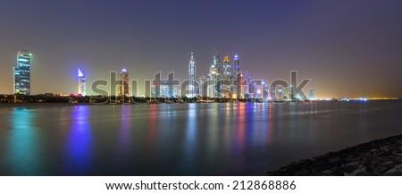 DUBAI, UAE - 2 APRIL 2014: Skyscrapers of Dubai Marina at night, UAE. Dubai Marina is a district in Dubai with artificial canal city who accommodates more than 120,000 people at Persian Gulf. - stock photo