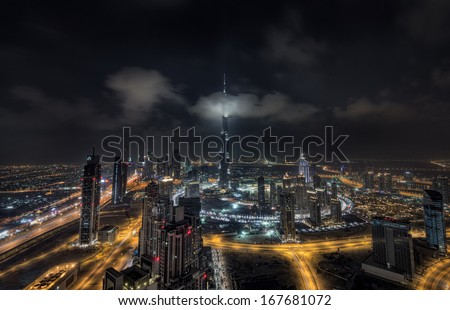 DUBAI, UAE - AUGUST 27: Scattered clouds passing by Burj khalifa and the downtown Dubai on August 27,2013 in Dubai, UAE - stock photo